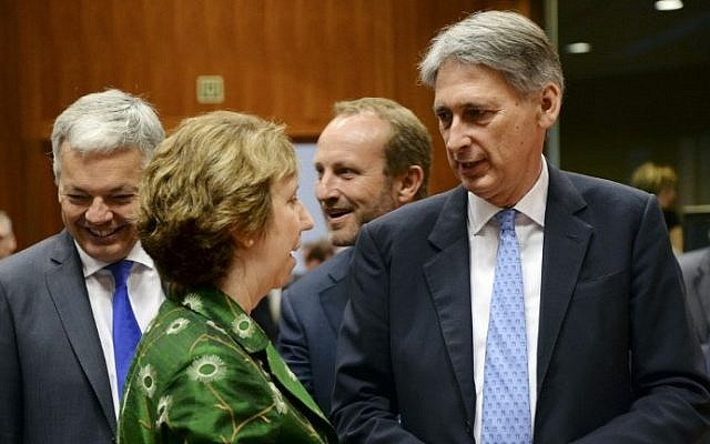European Union High Representative for Foreign Affairs and Security Policy Catherine Ashton, center, talks with British Foreign Affairs Minister Philip Hammond, right, prior to the start of the EU Foreign Affairs Council of Ministers held at the EU Council building in Brussels, on July 22, 2014. At left is Belgian Foreign Affairs Minister Didier Reynders.  photo credit: AFP/Thierry Charlier)