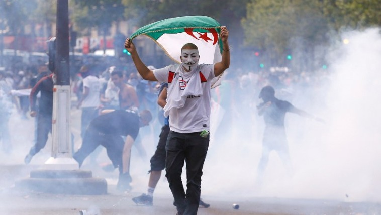 A protester wearing a Guy Fawkes mask and waving an Algerian flag walks through tear gas during clashes with French riot police officers, on the Republique square in Paris, in the aftermath of a banned demonstration against Israel's military operation in Gaza and in support of the Palestinian people, on July 26, 2014 (Photo credit: Kenzo Triboillard/AFP)