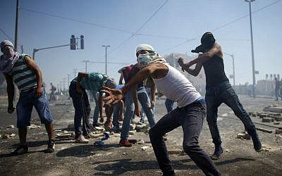 Masked Palestinian protesters throw stones towards Israeli police during clashes in the Shuafat neighborhood in East Jerusalem, July 3, 2014 (Photo credit: Thomas Coex/AFP)