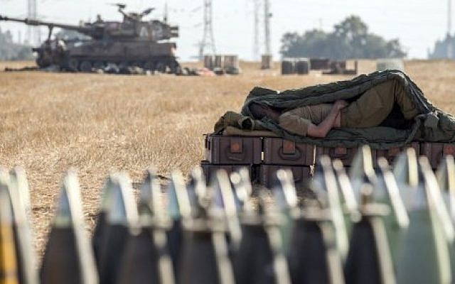 An Israeli soldier sleeps on an ammunition box near an 155mm artillery cannon stationed along the southern Israeli border with the Gaza Strip, Friday, July 11, 2014. (photo credit: Jack Guez/AFP)