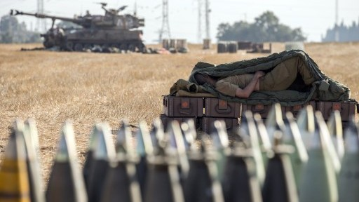 An Israeli soldier sleeps on an ammunition box near an 155mm artillery canon stationed along the southern Israeli border with the Gaza Strip, Friday, July 11, 2014. (photo credit: Jack Guez/AFP)