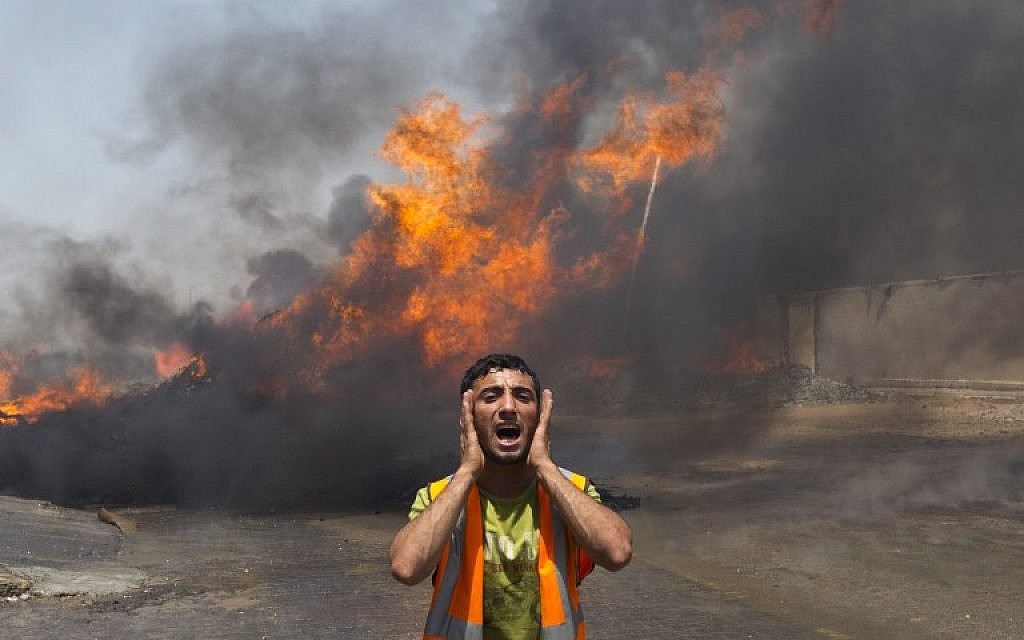 Palestinian firefighters try to extinguish fire at UN storehouse after an Israeli military strike in an area west of Gaza City on July 12, 2014. (photo credit: AFP/Mahmud Hams)