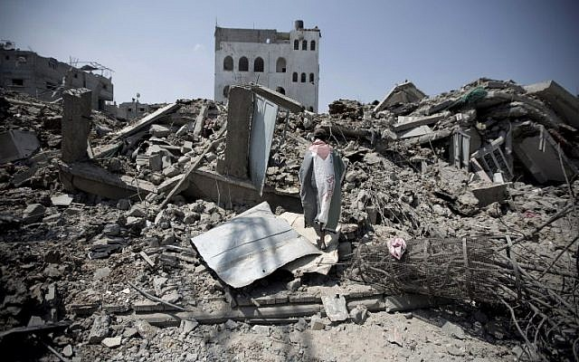 A Palestinian man, wrapped in his national flag, inspects the rubble of destroyed buildings and houses in the Shejaiya residential district of Gaza City, on July 28, 2014. (photo credit: AFP/MAHMUD HAMS)