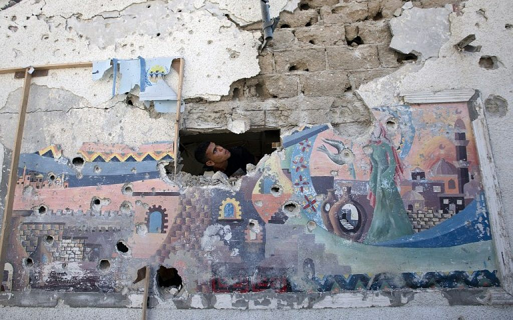 A Palestinian man inspects the damage at a UN school in the Jabaliya refugee camp in the northern Gaza Strip, July 30, 2014. (photo credit: AFP/Mahmud Hams)