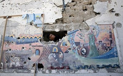 A Palestinian man inspects the damage at a UN school in the Jabalia refugee camp in the northern Gaza Strip, July 30, 2014 (photo credit: AFP/MAHMUD HAMS)