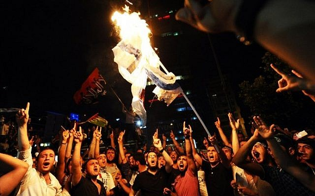 Turkish protestors set fire to an Israeli flag while shouting slogans during a demonstration against the Israeli military operation in Gaza, Saturday, July 19, 2014 in front of the Israeli Consulate in Istanbul. (photo credit: Ozan Kose/AFP)