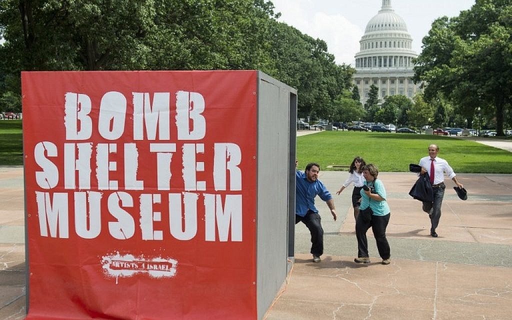People run towards a mock bomb shelter during a simulated attack by Hamas rockets as part of a multimedia art exhibit called The Bomb Shelter Museum which is modeled after bomb shelters in Israel, near the US Capitol in Washington, on July 22, 2014. (photo credit: AFP/Saul Loeb)