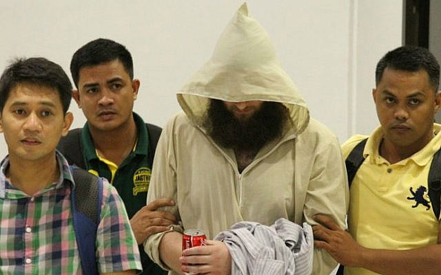 "Philippine Immigration officers escort Robert Edward Cerantonio (C), an Australian convert to Islam who used the internet to urge people to join ""jihad"" in Iraq and Syria, seen here in in Cebu City July 11, 2014. (photo credit: AFP)"