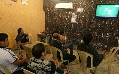 "Iraqi Raad Abdulhussein (C) and his friends sit watching on TV the 2014 FIFA World Cup round of 16 football match between Algeria and Germany on July 1, 2014 at the ""Facebook"" cafe in the Iraqi capital Baghdad. (photo credit: AFP/AHMAD AL-RUBAYE)"