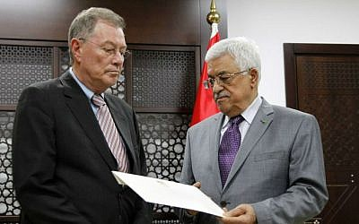 Palestinian Authority President Mahmoud Abbas (right) presents a letter to UN Special Coordinator for the Middle East Peace Process Robert Serry (left), at a meeting at Abbas's office in the West Bank city of Ramallah, on July 13, 2014. (photo credit: AFP/Abbas Momani)
