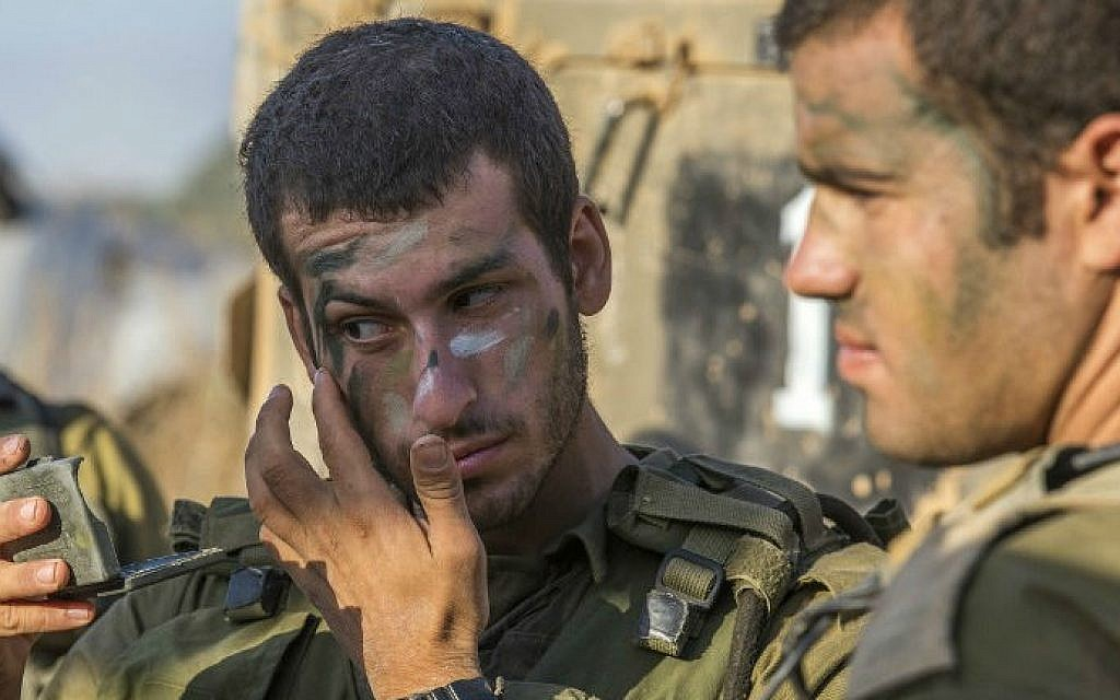 Israeli soldiers camouflage their faces at an army staging area along Israel's border with the Gaza Strip on July 30, 2014 (photo credit: AFP/JACK GUEZ)