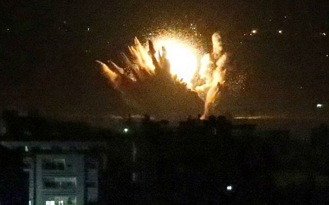 An IDF missile hits Palestinian buildings in Gaza City on July 17, 2014. Israel launched a ground operation in Gaza late Thursday on the 10th day of an offensive to stamp out rocket attacks from the Palestinian enclave, the army said. (photo credit: AFP/THOMAS COEX)