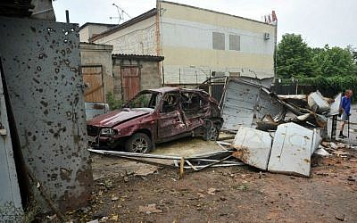 Local residents stand near a car destroyed after clashes between Ukrainian forces and pro-Russia militants in the eastern Ukrainian city of Lugansk on July 19, 2014. (photo credit: AFP/Alex Inoy)