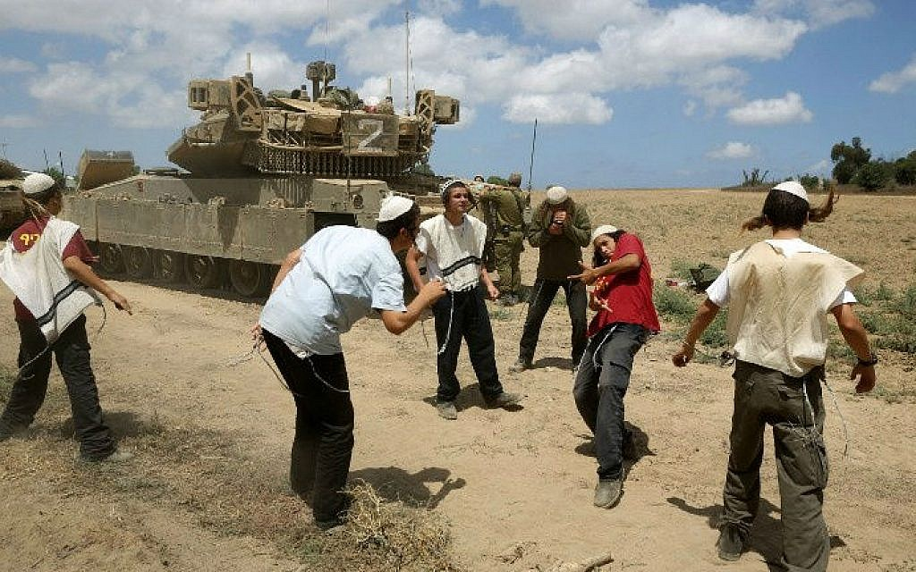 Young Orthodox Jews dance to support the soldiers at an army deployment area near Israel's border with the Gaza Strip, on July 17, 2014 (photo credit: AFP/Menahem Kahana)