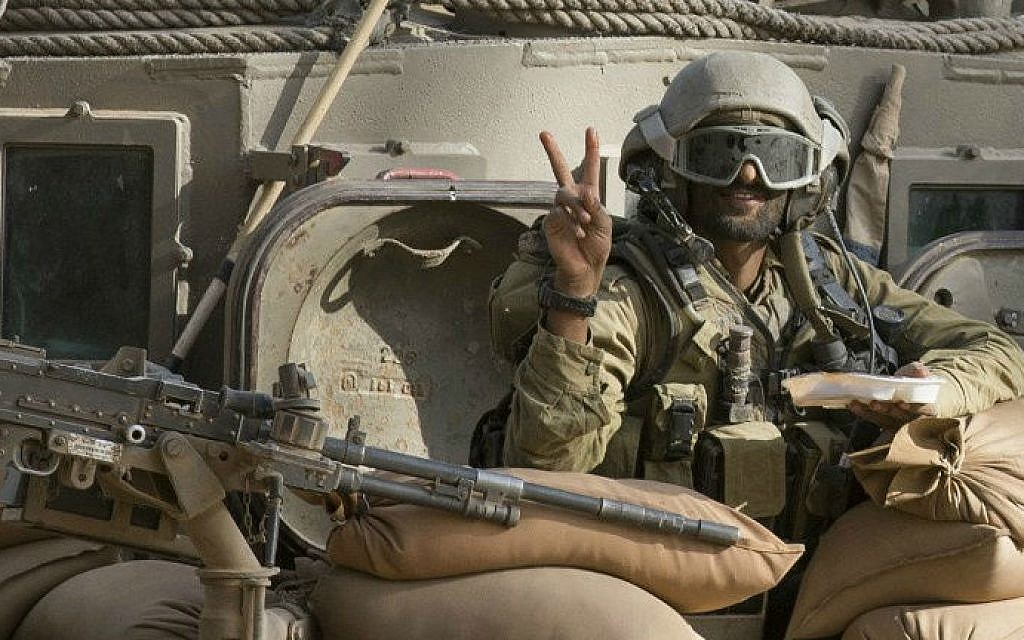 "An illustrative photo of an Israeli soldier flashing the ""V"" for victory sign from an armored personnel carrier (APC) at an army deployment area near Israel's border with the Gaza Strip on July 17, 2014 (photo credit: AFP/ Jack Guez)"