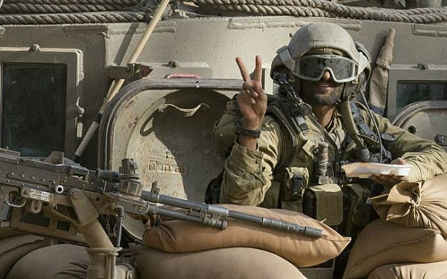 An illustrative photo of an Israeli soldier flashing the 'V' for victory sign from an armored personnel carrier (APC) at an army deployment area near Israel's border with the Gaza Strip on July 17, 2014 (AFP/ Jack Guez)