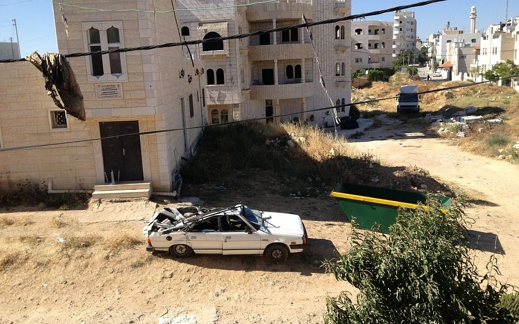 A car parked in the courtyard of the Abu Aysha home in Hebron was crushed by falling bricks from the building's wall and moved outside (photo credit: Elhanan Miller/Times of Israel)