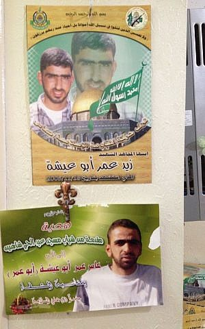 Amer Abu Ayshas certificate of health hangs on the family wall beneath a poster of his brother, Zaid, killed in 2005 (photo credit: Elhanan Miller/Times of Israel)