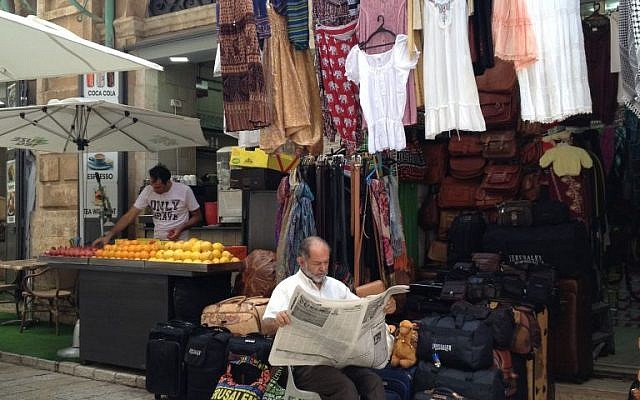 A man reads the headlines of Al-Quds daily in the Old City of Jerusalem, July 13, 2014 photo credit: Elhanan Miller/Times of Israel)