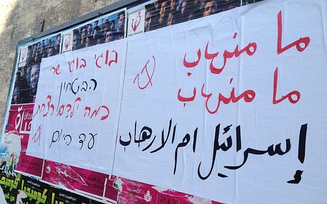 Posters in Arabic and Hebrew read 'Israel is the source of terror' and 'Boogie, how many children have you killed so far' (photo credit: Elhanan Miller/Times of Israel)