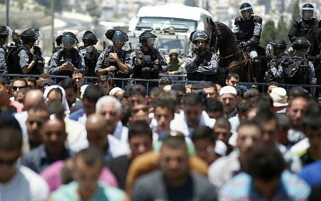 Israeli police stand guard as Muslim men pray in the middle of a street outside the Old City in East Jerusalem on July 4, 2014, during the first Friday prayer of the holy fasting month of Ramadan (photo credit: AFP/ Thomas Coex)
