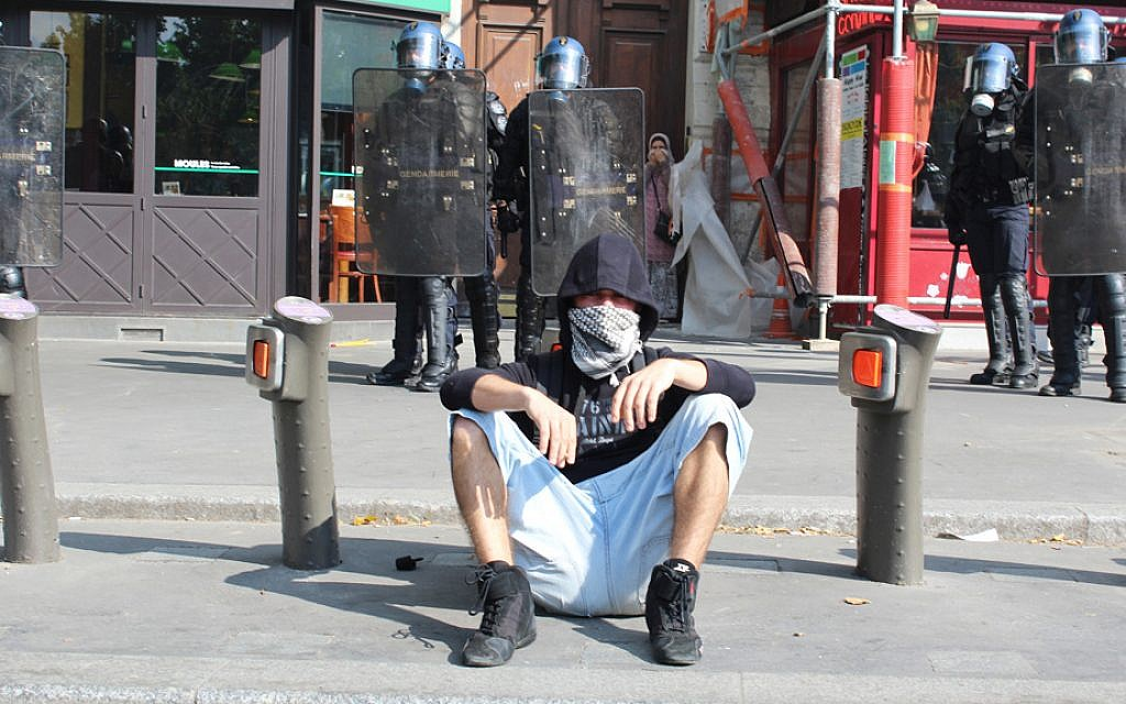 A pro-Palestinian protestor rests on a Parisian sidewalk while riot police observe on Saturday, July 26, 2014. (Glenn Cloarec/The Times of Israel)