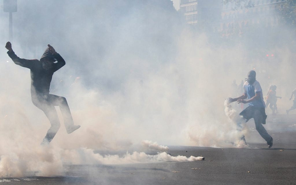 Youth jump over smoke bombs set off during the illegal Parisian protest on Saturday, July 26, 2014. (Glenn Cloarec/The Times of Israel)