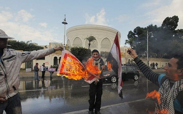 "Egyptian protesters burn an Arabic banner reading ""Hamas, brotherhood, Qatar and America, are Egyptian enemies,"" in front of the presidential palace in Cairo, Egypt, Friday, February 1, 2013 (photo credit: AP/Amr Nabil)"