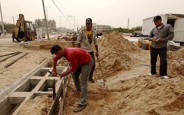 In this Monday, April 8, 2013 photo, Palestinians work on a Qatar-funded road in Gaza City photo credit: AP/Hatem Moussa)