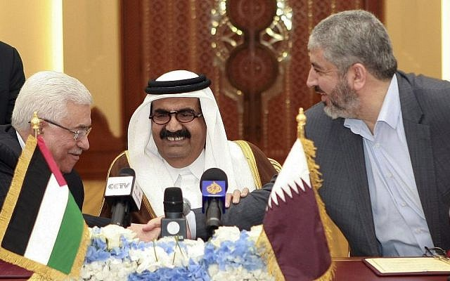Palestinian authority President Mahmoud Abbas, left, shakes hands with Hamas leader Khaled Mashaal, right, as the Emir of Qatar, Sheikh Hamad bin Khalifa Al Thani, center, looks on, after signing an agreement in Doha, Qatar, Monday, February 6, 2012 (photo credit: AP/Osama Faisal)