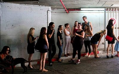 Israelis take cover in an underground parking garage as siren sounds during rocket attack fired by Palestinian militants from Gaza in Tel Aviv, Israel, Thursday, July 10, 2014. (photo credit: AP/Oded Balilty)