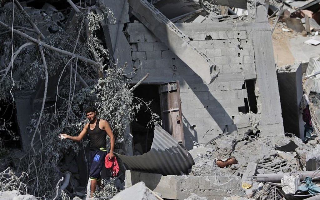 A Palestinian shows his pet bird which he managed to catch amid the rubble of houses destroyed by Israeli strikes in Beit Hanoun, northern Gaza Strip, Sunday, July 27, 2014. (Photo credit:AP/Lefteris Pitarakis)