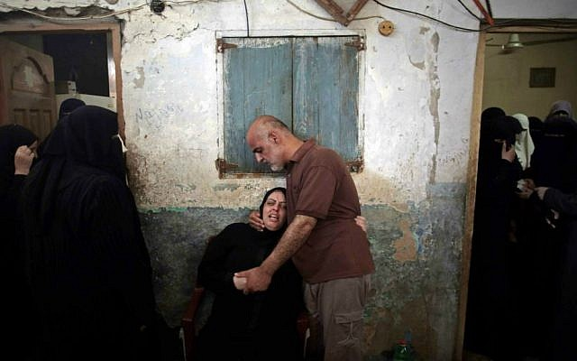 Palestinian relatives of eight members of the Al Haj family, who were killed in a strike early morning, grieve in the family house during their funeral in Khan Younis refugee camp, southern Gaza Strip on Thursday, July 10, 2014. (AP Photo/Khalil Hamra)