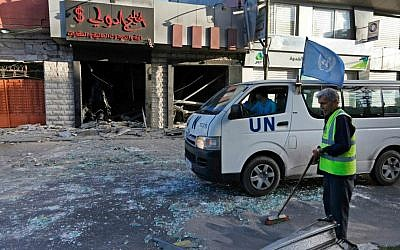 A Palestinian municipality worker sweeps glass from the street, as a UN vehicle drives past a damaged money-exchange post, following an overnight Israeli missile strike in Gaza City, Thursday, July 17, 2014. (photo credit: AP/Lefteris Pitarakis)