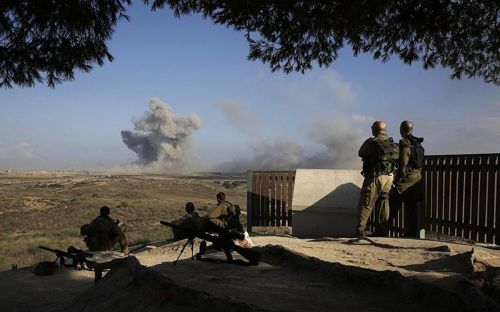 Israeli soldiers observe bombings of Gaza before a 12-hour cease-fire, seen from the border of Israel and the Gaza Strip on Saturday, July 26, 2014. (photo credit: AP/Tsafrir Abayov)