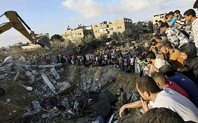 Palestinians gather around the rubble of a building on Saturday July 26, where at least 20 members of the Al Najar extended family were reported killed by an Israeli strike in Khan Younis, in the southern Gaza Strip. (photo credit:AP/Eyad Baba)