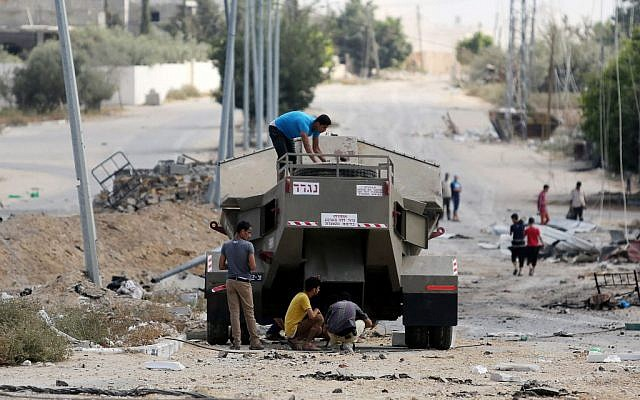 Palestinian men climb on Israel's military vehicle that was left behind by the forces in Gaza City's Shejaiya neighborhood, Saturday, July 26, 2014. (photo credit: AP/Hatem Moussa)