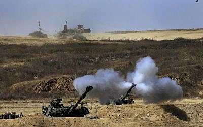 An Israeli tank fires towards Gaza, near the Israel and Gaza border on the morning of Sunday, July 27, 2014. (Photo credit: AP/Tsafrir Abayov)