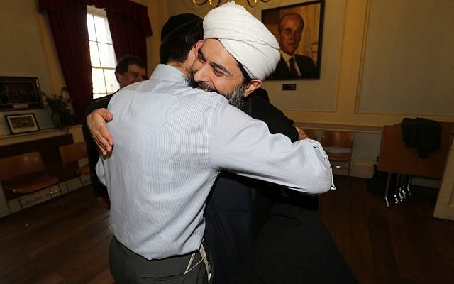 Rabbi Natan Levy and Muslim leader Sheikh Ibrahim Mogra embrace at a Holocaust exhibition  at  the Board of Deputies of British Jews in 2013. (courtesy: Natan Levy)