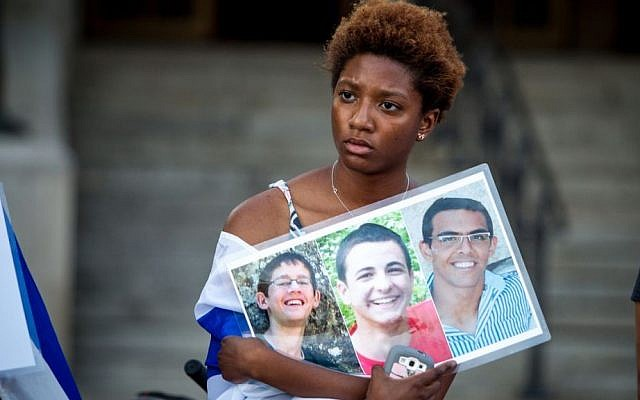 A Boston area student holds up photos of the three Israeli students who were murdered in the West Bank (photo credit: Elan Kawesch)