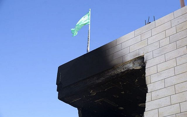 A Hamas flag flutters above the Abu Aysha home in Hebron a day after the IDF stormed and detonated it. Security forces demolished the home overnight Sunday, August 18, 2014. (photo credit: courtesy/Queralt Gómez Cuberes)