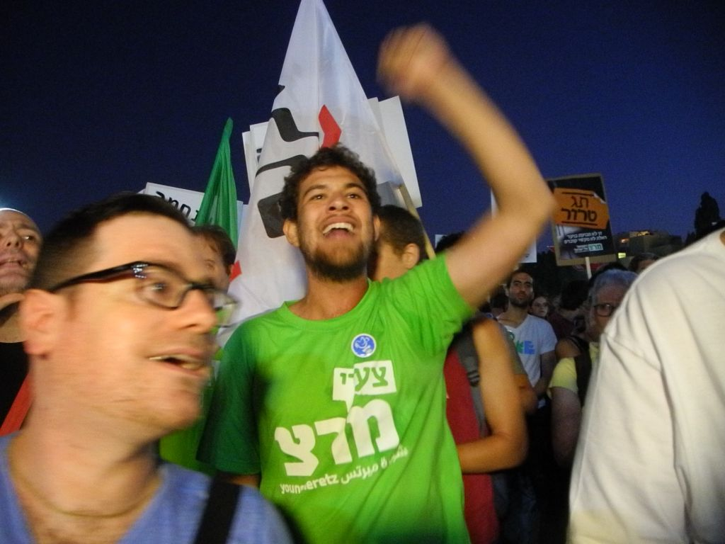 "Meretz activists heckling MK Amram Mitzna (Hatnua) with calls of  ""quit!"" and ""leave the coalition!"" during an anti-incitement rally in Tel Aviv, July 03, 2014. (photo credit: Melanie Lidman)"