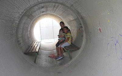 Devorah Israeli, of Nitzan, with 8-year-old Idan and 6-month-old Ron in the sewage pipe bomb shelter next to her home, which residents complain is not sufficient protection (photo credit: Melanie Lidman/Times of Israel)