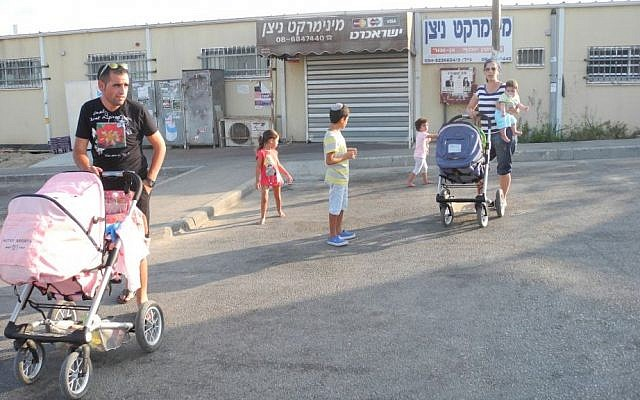 Deborah Israeli and Eviatar Cohen with their children outside the convenience store and grocer on Sunday, both of which were closed due to the situation. photo credit: Melanie Lidman/Times of Israel)