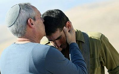 A religious Jewish father kisses his son on the forehead.
