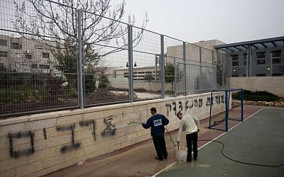 Workers clean off the Graffiti at the Jewish-Arab bilingual school in Jerusalem stating 'death to Arabs' and 'Kahana was right,' Feb 7, 2012 (photo credit: Flash90)
