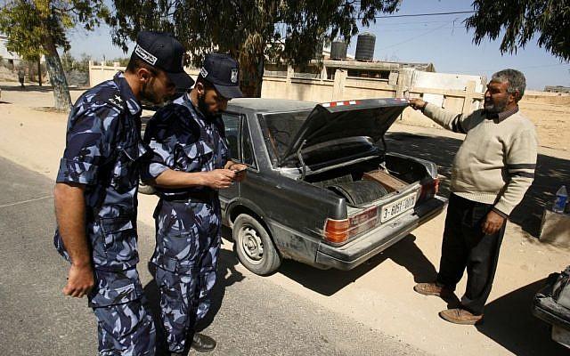 A Hamas security officers checks IDs after stopping a car at a checkpoint on the outskirts of the border between Rafah and Israel to prevent Palestinian collaborators from escaping into Israel, April 15, 2013 (Abed Rahim Khatib/Flash90)