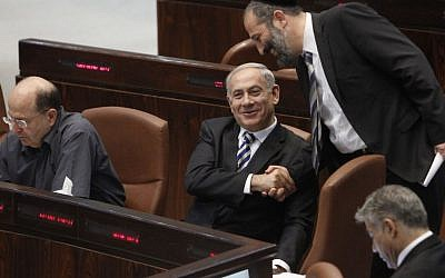 Prime Minister Benjamin Netanyahu shakes hands with Shas chairman Aryeh Deri during a plenum session in the Knesset, June 2013. (file photo credit: Miriam Alster/Flash90)