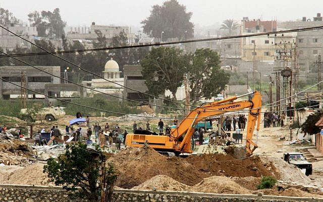 File: A picture taken from the southern Gaza Strip shows Egyptian soldiers using bulldozers as they demolish houses in search of tunnels on the border with Egypt and the southern Gaza Strip the Rafah on March 17, 2014. (Abed Rahim Khatib/Flash90)