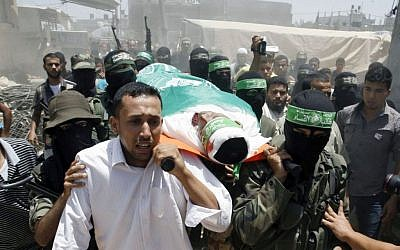 Palestinian militants of the Izz ad-Din al-Qassam Brigades, Hamas's armed wing, carry the body of militant Mohammed Obied during his funeral in the town of Deir al-Balah, in the central Gaza Strip on June 30, 2014 (photo credit: Abed Rahim Khatib/Flash90)